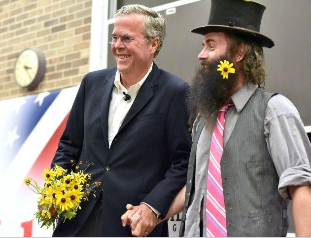Jeb Bush holds hands with Rod Webber after receiving flowers of peace on the campaign trail.