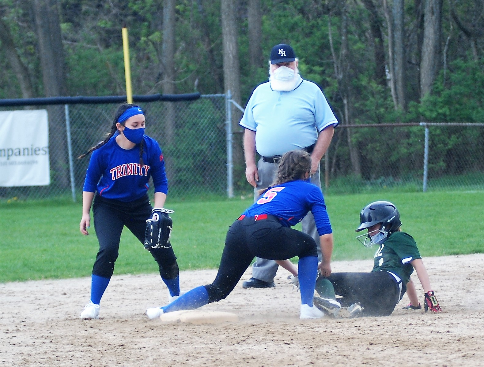 Trinity shortstop Emma Service tags Central's Catherine Jones for the out.